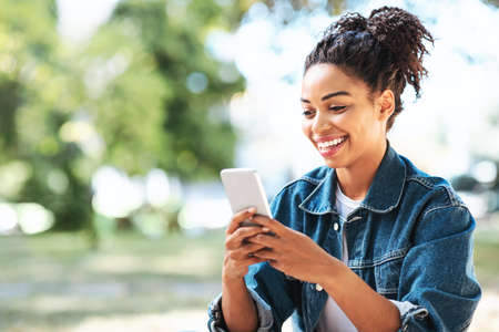 Happy Black Girl Using Mobile Phone App Browsing Internet Sitting In Park Outside. Empty Space For Text