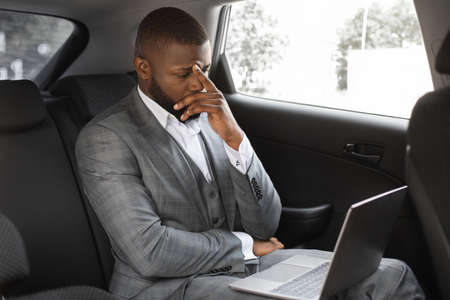 Worried black guy manager with laptop going by taxi to job. Upset african american businessman having bad day, working on laptop while going to business meeting by car, copy space