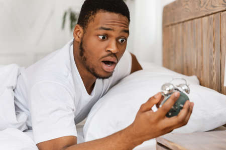 Oversleeping. Overslept African American Man Looking In Shock At Broken Alarm Clock Waking Up In The Morning, Lying In Bed At Home. Late For Work, Bad Morning, Tardiness Concept