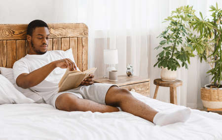 Read More. African American Man Reading Bestseller Book Lying In Cozy Bed Relaxing In Bedroom At Home. Black Guy Enjoying Lazy Morning. Weekend Leisure And Relaxation Concept