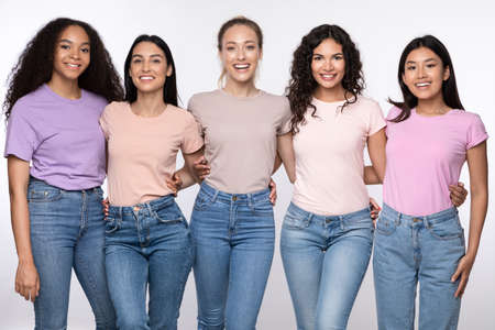 Group Of Five Cheerful Multicultural Ladies Embracing Posing Standing Over White Background, Smiling To Camera. Female Friendship, Diversity And Unity Concept. Studio Shot