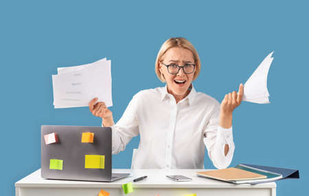 Stressed businesswoman with papers feeling angry or having nervous breakdown near laptop at desk, blue studio background. Corporate employee suffering from negative emotions or work overload. Panorama
