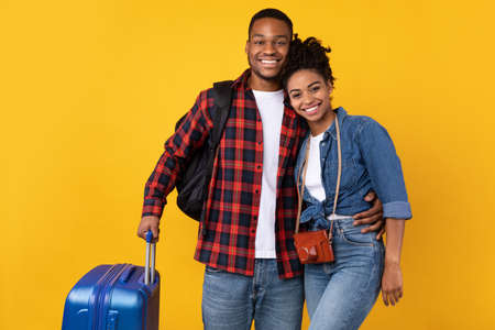 Cheerful African American Tourists Couple Traveling Standing With Suitcase Luggage Ready For Vacation Posing On Yellow Studio Background. Travel Together, Tourism, Holiday Trip Concept Imagens