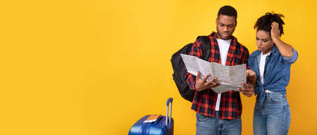 African Tourists Couple Having Problem Planning Vacation Holding Map Choosing Destination Standing Over Yellow Background In Studio. Travel Navigation Problems Concept. Panorama With Copy Space