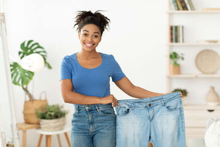 Weight Loss. Happy Slim Black Woman Showing Old Oversize Jeans After Successful Diet Slimming Standing At Home