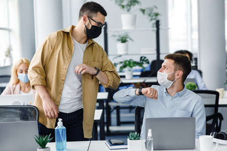 Safe hello at work during COVID-19 epidemic and social distance. Young men in protective masks greet with elbows at workplace with laptop and antiseptic in modern office interior, copy space