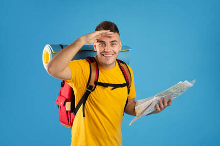 Happy millennial tourist with camping equipment and map looking at camera on blue studio background. Smiling handsome backpacker plotting his travel route