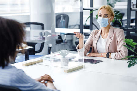 Modern interview and meeting with manager during coronavirus quarantine. African american lady speaks to business woman in protective mask through glass partition in office interior