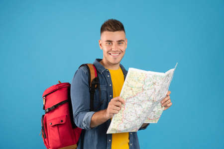 Positive young hiker with backpack and map planning his weekend camping trip route on blue studio background. Portrait of happy millennial traveler ready to go trekking