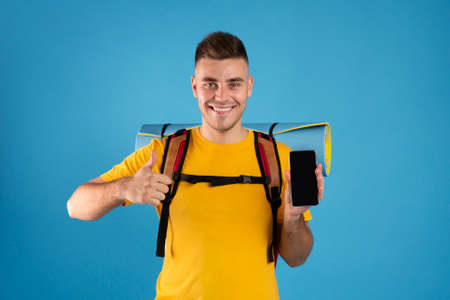 Online trip booking concept. Handsome young man showing mobile phone with empty screen and making thumb up gesture on blue studio background. Space for your website design Stock fotó