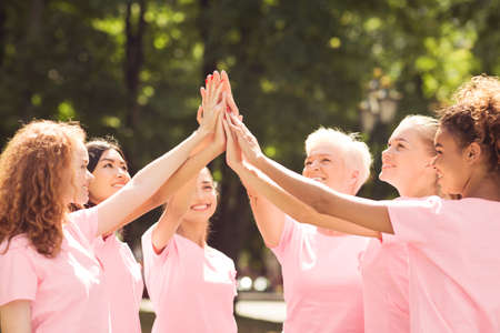 Oncology Volunteers. Smiling Breast Cancer Patients In Pink T-Shirts Giving High Five During Support Group Meeting Outdoors. Selective Focus