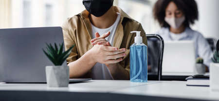 Focus on antiseptic to protect against covid virus. Guy disinfects his hands, sitting at table at workplace with laptop, working in interior of modern office, panorama, copy space