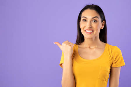 Cool Offer Concept. Portrait Of Excited Young Surprised Woman Pointing Finger At Copy Space Isolated Over Purple Studio Background. Crazy Emotional Female Model Indicating Free Space, Banner
