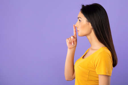 Shh, Keep Silence, Be Quiet Concept. Side view profile portrait of young woman putting finger on lips, lady showing hush sign, looking at copy space, isolated over purple studio background wall