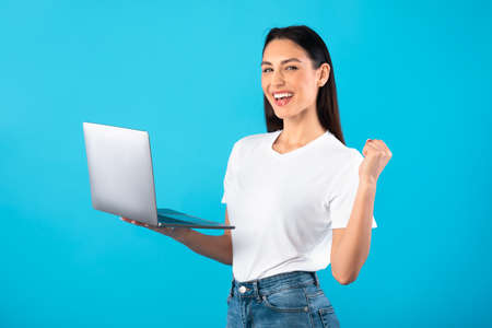 Great Job. Portrait of excited lady holding laptop computer at studio making winner gesture. Emotional woman celebrating online win, good deal or business success using pc isolated over blue wall