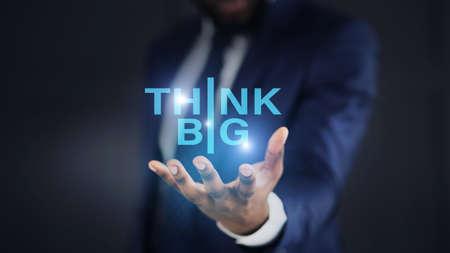 Black businessman holding think big illuminated text on his palm, collage