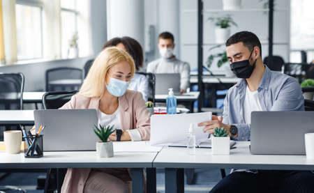 Social distance and work with documents in modern office. Millennial man and woman in protective masks in workplace with laptops and antiseptic, talk after quarantine covid-19, panorama, copy space