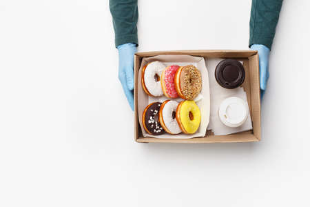 Coffee with sweets for two takeaway during covid outbreak. Waiter in rubber gloves gives box of donuts with glaze and crumb and cups of coffee isolated on white background, top view, flat lay, copy space