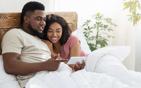 Happy black lovers holding smartphone, watching photos or videos together, lying on bed at home, copy space. African american young man and woman using mobile phone in bedroom, having fun together