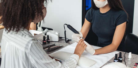 Professional manicure master in protective mask makes manicure procedure with electric device to african american female client at table with equipment, panorama, cropped