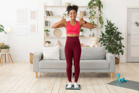 Fit Black Lady After Weight Loss Standing On Scales Gesturing Thumbs-Up Approving Fitness Lifestyle Posing At Home. Successful Weight-Loss Concept. Full Length, Free Space For Text