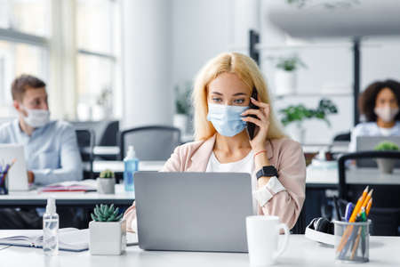 Working in modern office after returning from quarantine. Millennial lady in protective mask speaks on phone and looks at laptop at table with antiseptic in office interior, empty space