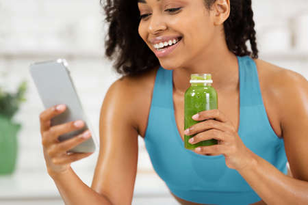 Enjoying Drink. Black woman in blue sports bra using smartphone, holding homemade vegetable smoothie juice for breakfast. Lady surfing internet and social media in the morning at kitchen