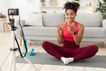 Fitness Blogging. African Blogger Woman Making Workout Video Motivating Stay Fit At Home, Sitting On Gymnastics Mat Near Camera. Domestic Sporty Routine Concept. Selective Focus