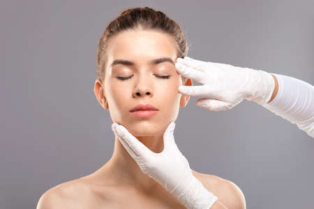 Concept of modern beauty. Attractive young woman getting treatment at cosmetology clinic, changing her appearance. Plastic surgeon touching beautiful lady face, grey studio background, copy space