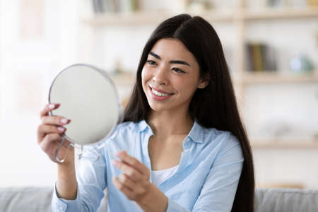 Beautiful Asian Woman Holding Magnifying Mirror At Home, Looking At Her Reflection, Enjoying Look Of Her Perfect Face Skin And Smiling, Happy With Results After Beauty Treatments, Free Space Stockfoto