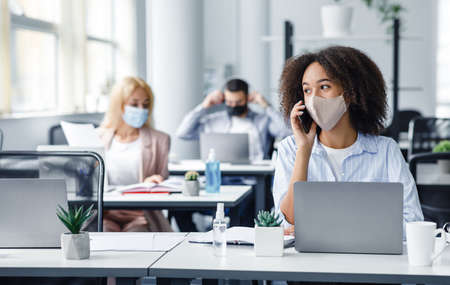Working with clients remotely after returning from quarantine. African american woman in protective mask speaks on phone, sitting at table with laptop in modern office interior with colleagues, empty space