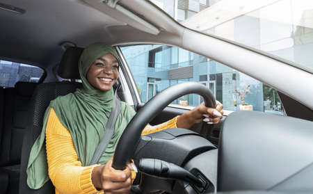 City Ride. Portrait Of Happy Smiling Black Muslim Lady In Headscarf Driving Modern Car, Wearing Seatbelt, Holding Steering Wheel, Making Test Drive For New Automobile, Looking At Road, Low Angle Shot 写真素材