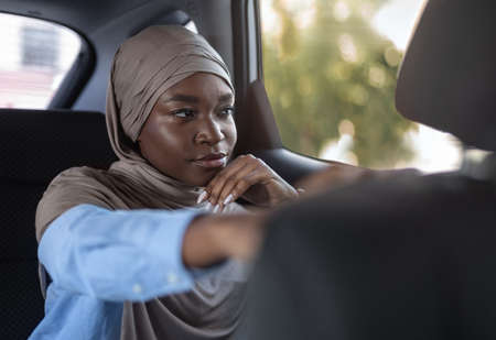 Confident black muslim businesswoman sitting in car and looking through window, going to office by taxi, placing hand on front seat, thinking about something, wearing hijab, free space