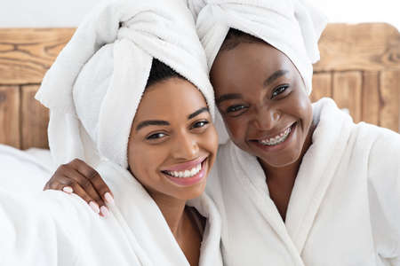 Two pretty cheerful african american young women having ladies day at home, wearing bathrobes, sitting on bed. Black female friends embracing and smiling, bedroom interior, closeup portrait