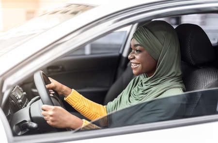 Cheerful African Muslim Lady In Headscarf Driving New Car In City, Riding Her New Vehicle, Got Driving License, Holding Steering Wheel And Using Seatbelt, Side View Shot With Copy Space