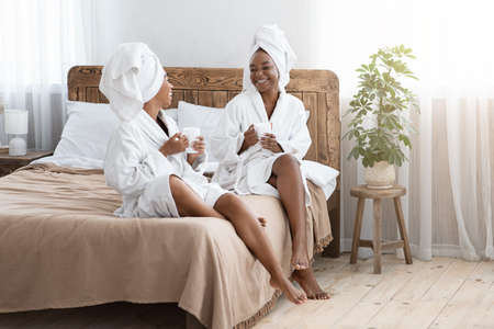 Beautiful black ladies sitting on bed, wearing bathrobes, drinking coffee and having conversation, copy space. Two african american female friends spending time together at home, spa concept