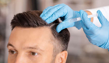 Handsome middle aged man getting hair treatment at beauty salon. Attractive man having mesotherapy session at beauty salon, therapist hand in protective glove making injection with syringe, closeup