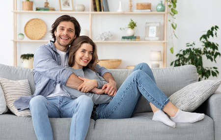 Beautiful couple hugging while sitting on couch at home, spending weekend together, copy space. Young man and woman in love resting at living room, posing at camera, family, love, marriage concept