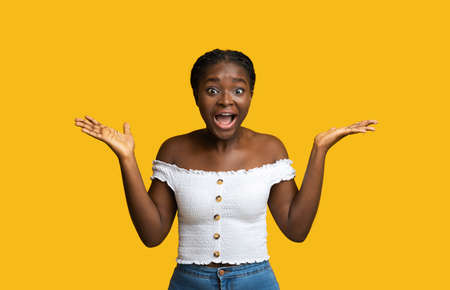 Happy Shock. Emotional African Lady Exclaiming With Excitement, Looking At Camera And Raising Hands, Standing With Opened Mouth Isolated On Yellow Background, Amazed By Something, Copy Space
