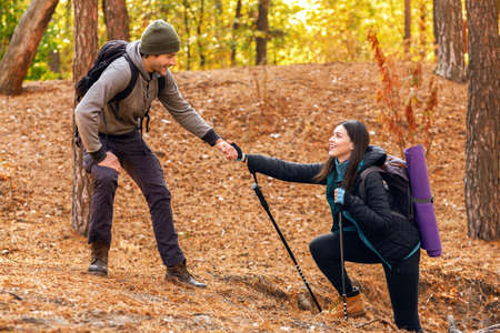 Handsome man hiker helping his girlfriend uphill in forest, couple hiking together