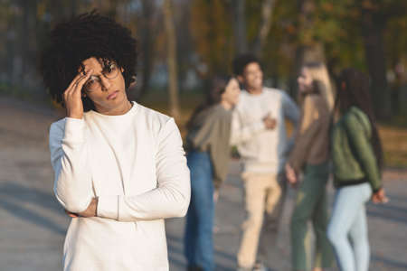 Sad african teenager touching his head, had arguement with his multiracial friends in park
