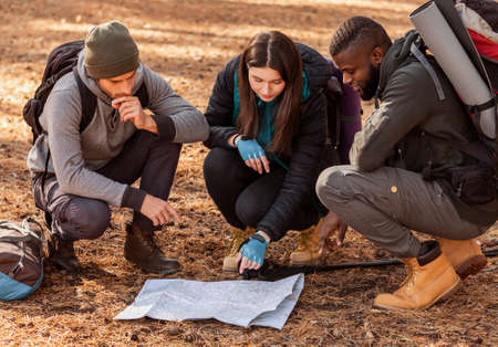 Confused group of multiethnic hikers looking at map, lost in forest Banque d'images