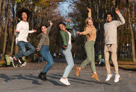 Crazy young multiethnic group of friends jumping up, having fun at public park