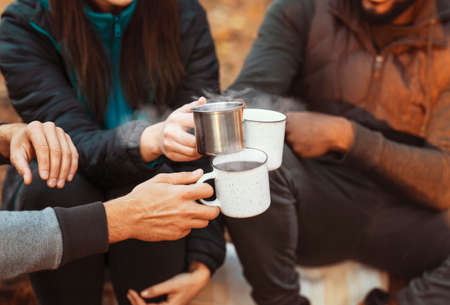 Warming up in camping. Hands of international hikers cheering up with camping cups, camping in forest, closeup