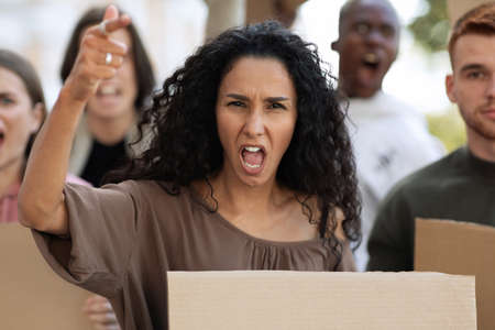 Mixed race woman leading international group of motivated demonstrators with empty placards on the street. Strikers with blank slogan boards yelling and raising fists up, fighting for human rights Stock Photo