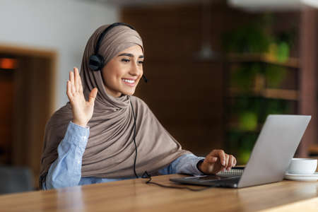 Smiling arab woman having video call while resting at cafe, using laptop and headset, empty space. Cheerful young lady in hijab waving at laptop screen, attending video conference, drinking coffee