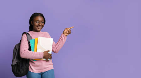 Young black female student pointing aside at copy space with finger, recommending educational offer or promo, showing free place, posing on purple background, holding workbooks and backpack, panorama