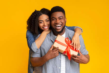 Cheerful african man got present from his loving girlfriend, posing with gift box and smiling at camera while his woman cuddling him from back