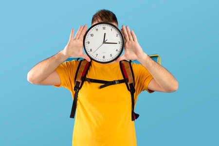 Time to travel concept. Young man with camping equipment holding clock in front of his face over blue studio background. Millennial guy ready to start his hiking journey or vacation