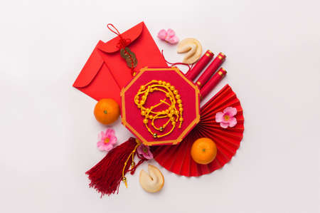 Flat lay Chinese new year tangerine, plum blossoms and other traditional accessories on white background